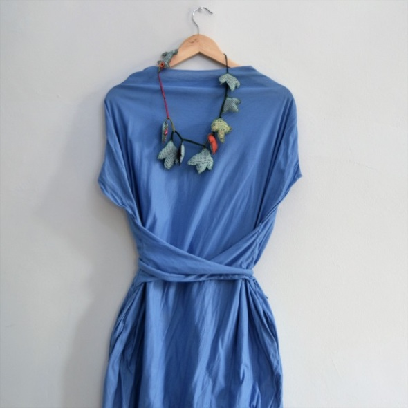Blue dress in cotton with simple comfortable lines adjustable at the waist with two fabric strips that hang both sides of the dress